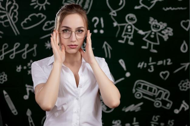 Jeune enseignant se tient près du tableau noir dans la salle de classe