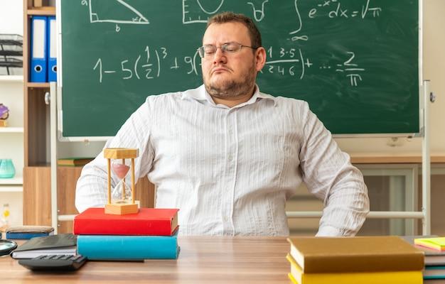 Jeune enseignant strict portant des lunettes assis au bureau avec des fournitures scolaires en classe en gardant les mains sur la taille en regardant le sablier