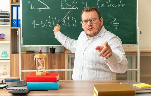 Jeune enseignant strict portant des lunettes assis au bureau avec des fournitures scolaires en classe regardant à l'avant pointant vers le tableau avec un bâton de pointeur regardant et pointant vers l'avant