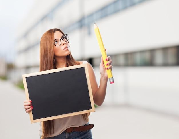 Jeune enseignant avec tableau noir et un crayon