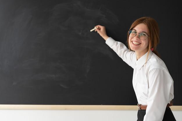 Jeune enseignant avec le tableau noir écrit à la craie