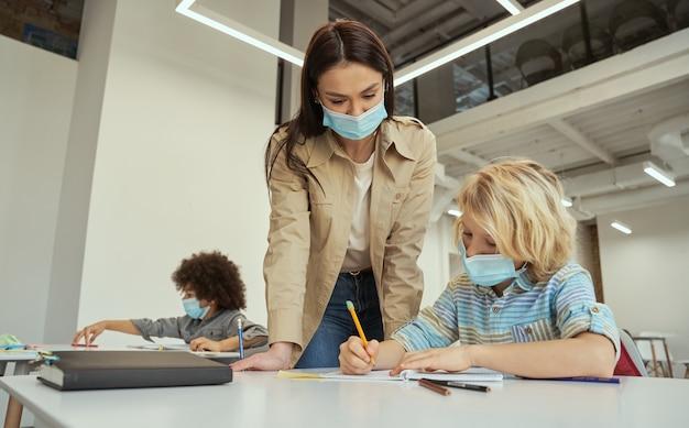 Jeune enseignante attentionnée portant un masque protecteur aidant un petit garçon à faire la tâche aux enfants