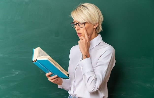 Jeune enseignante blonde concentrée portant des lunettes en classe debout en vue de profil devant le tableau tenant et lisant un livre en gardant la main sur le menton