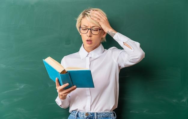 Jeune enseignante blonde concernée portant des lunettes en classe debout devant le tableau en gardant la main sur la tête tenant et lisant un livre