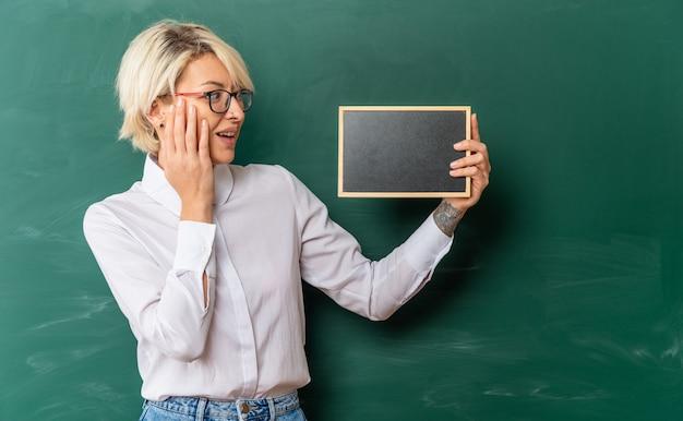 Jeune enseignante blonde excitée portant des lunettes en classe debout devant un tableau montrant un mini tableau noir le regardant en gardant la main sur le visage avec un espace de copie