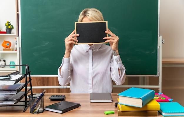 Jeune enseignante blonde portant des lunettes assis au bureau avec des fournitures scolaires en classe tenant un mini tableau noir devant le visage