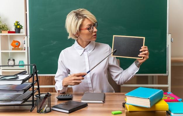 Jeune enseignante blonde portant des lunettes assis au bureau avec des outils scolaires en classe montrant un mini tableau noir le regardant pointé vers lui avec un bâton de pointeur