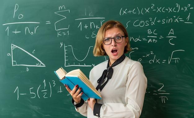 Jeune enseignante effrayée portant des lunettes debout devant un tableau noir tenant un livre en classe