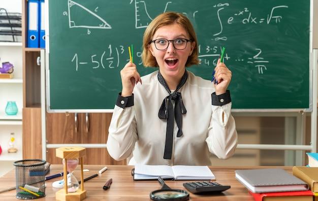 Jeune enseignante excitée est assise à table avec des fournitures scolaires tenant un crayon en classe