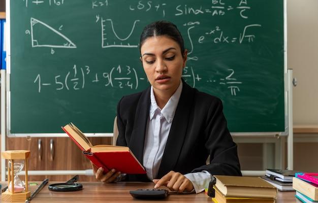 Une jeune enseignante impressionnée est assise à table avec des fournitures scolaires tenant un livre et regarde une calculatrice dans sa main en classe