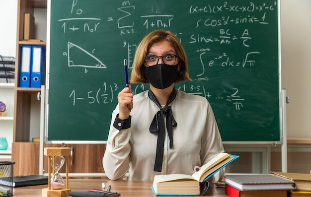 Une jeune enseignante impressionnée portant des lunettes et un masque médical est assise à table avec des outils scolaires tenant un stylo en classe