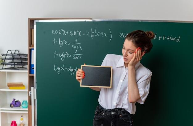 Jeune enseignante de mathématiques excitée debout devant un tableau montrant et regardant un mini tableau noir en gardant la main sur le visage en classe