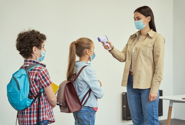 Jeune enseignante portant un masque de protection mesurant la température des enfants avec du numérique