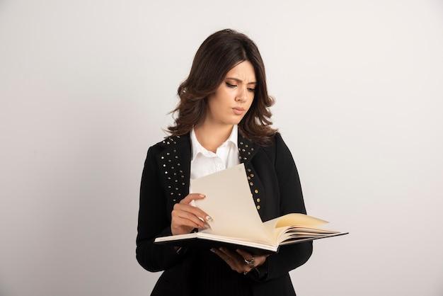 Jeune enseignante regardant à travers le cahier sur blanc.