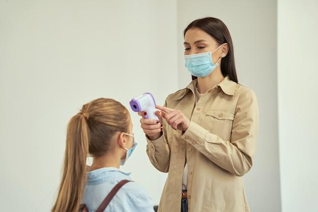 Jeune enseignante séduisante portant un masque de protection écolière de dépistage à l'aide du numérique