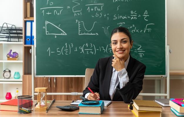 Une jeune enseignante souriante est assise à table avec des fournitures scolaires en écrivant quelque chose qui a attrapé le menton en classe