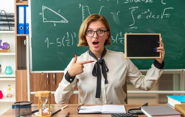 Une jeune enseignante surprise portant des lunettes est assise à table avec des fournitures scolaires tenant et pointe vers un mini tableau noir en classe