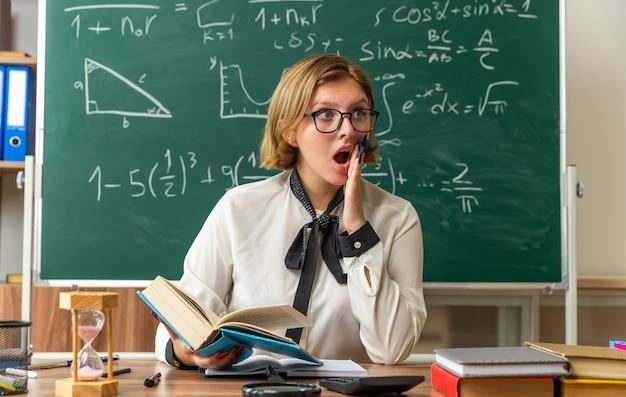 Une jeune enseignante surprise portant des lunettes est assise à table avec des outils scolaires tenant un livre mettant la main sur la joue en classe