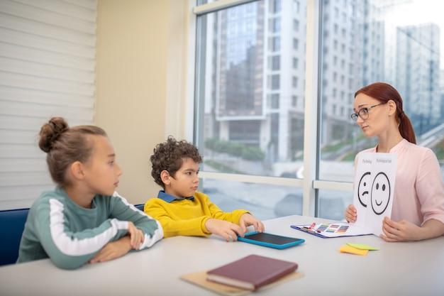 Une jeune enseignante utilisant des images emoji pendant sa leçon