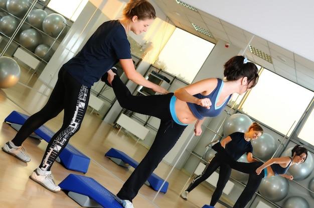 Un jeune entraîneur blanc caucasien blond aide à une femme brune à faire de l'exercice physique au gymnase