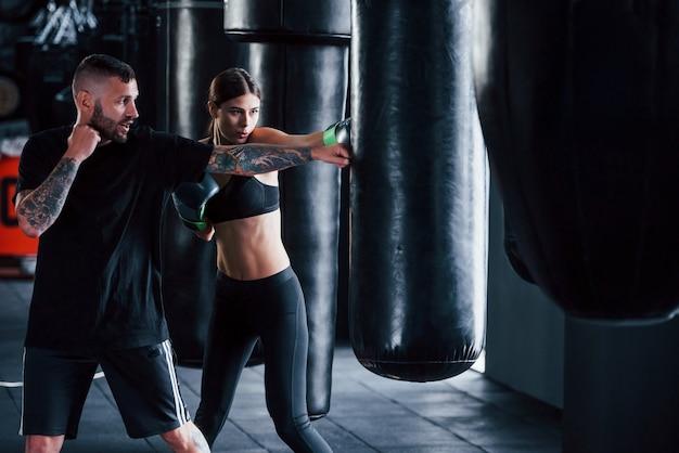 Jeune entraîneur de boxe tatoué enseigne jeune femme dans la salle de gym.