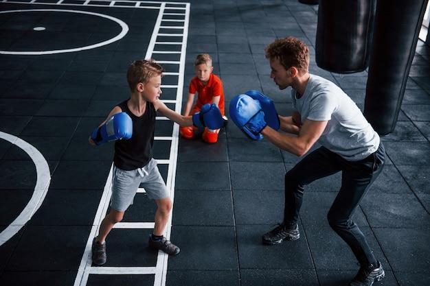 Un jeune entraîneur enseigne le sport de boxe aux enfants dans la salle de gym.