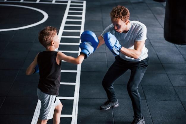 Un jeune entraîneur enseigne le sport de boxe pour enfants dans la salle de sport.