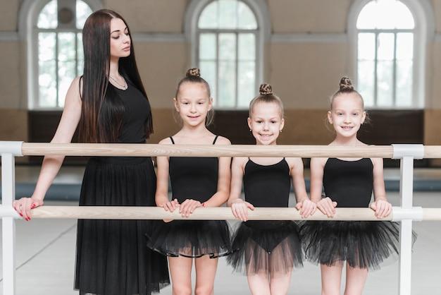 Jeune entraîneur féminin avec ses trois ballerines debout derrière la barre
