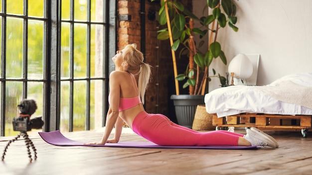 Jeune entraîneur de femme mince en forme sportive pratiquez la formation en ligne vidéo instructeur de yoga méditer, se détendre respirer siège facile pose concept de mode de vie sain