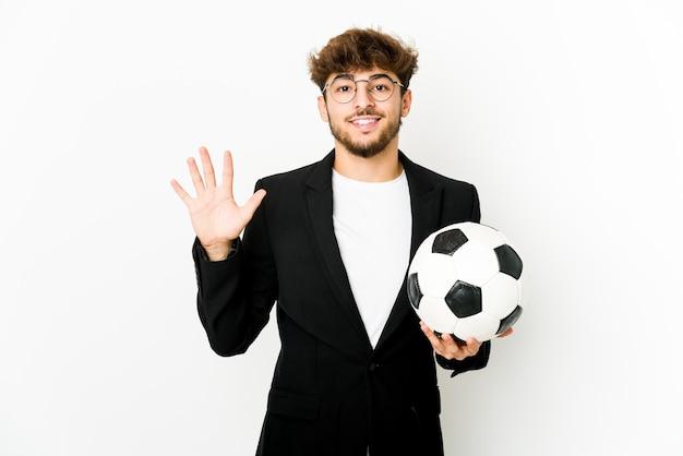 Jeune entraîneur de football indien isolé souriant gai montrant le numéro cinq avec les doigts.
