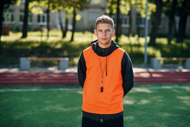 Jeune entraîneur de football professionnel dans un gilet orange