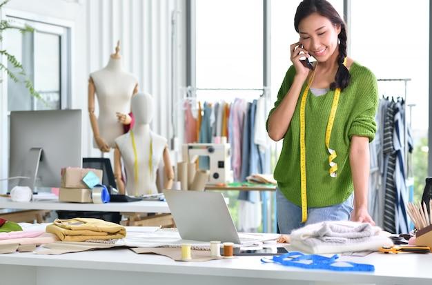 Jeune entrepreneur asiatique / créatrice de mode travaillant en studio