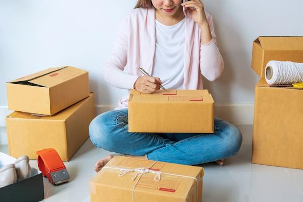 Jeune entrepreneur asiatique, parler au téléphone avec le client