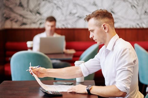 Jeune entrepreneur assis à table de café et faire des calculs