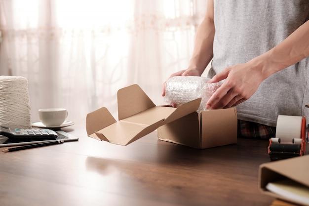 Jeune entrepreneur en démarrage emballant des produits en plastique antichoc pour envoi au client