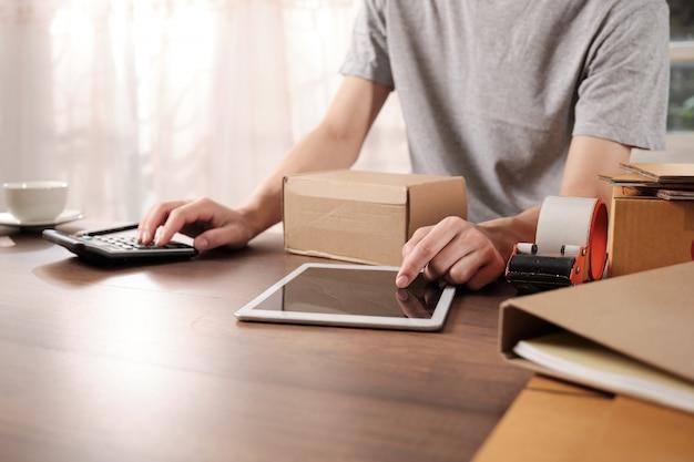 Jeune entrepreneur en démarrage vérifie sa commande sur tablette le matin