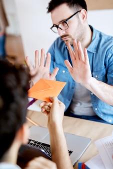 Le jeune entrepreneur honorable refuse un pot-de-vin dans l'enveloppe. concept de corruption pour les transactions illégales au bureau.
