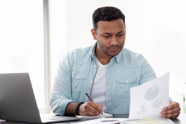 Jeune entrepreneur indien pensif parcourant des documents tout en étant assis au bureau à la maison ou au bureau, analyse les rapports de vente, indépendant travaillant assis à un bureau