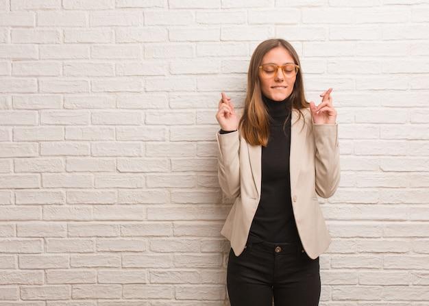 Jeune entrepreneur jolie femme d'affaires croise les doigts pour avoir de la chance