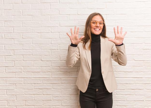 Jeune entrepreneur jolie femme d'affaires montrant le numéro dix