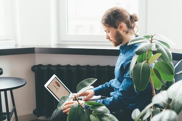 Jeune entrepreneur masculin à la recherche de tableaux et de graphiques sur ordinateur portable pendant la pause de travail