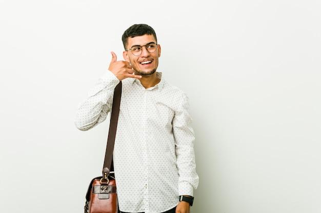 Jeune entrepreneur occasionnel hispanique montrant un geste d'appel de téléphone portable avec les doigts.