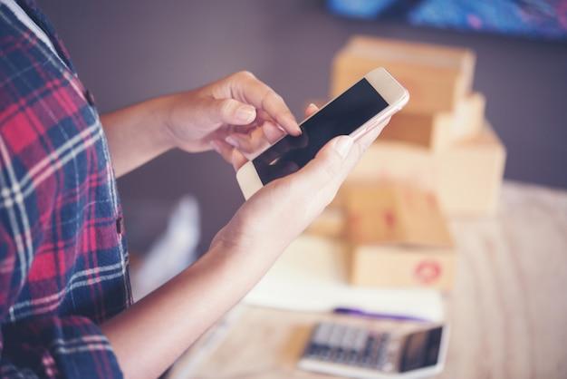 Jeune entrepreneur, propriétaire d'entreprise adolescent travaille à la maison, boîte pour la livraison