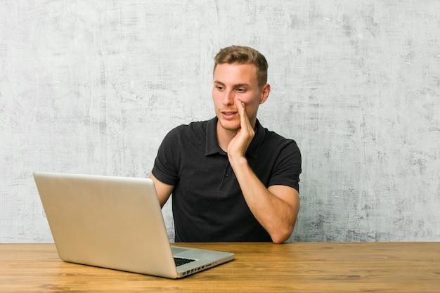 Un jeune entrepreneur qui travaille avec son ordinateur portable sur un bureau raconte une nouvelle secrète sur le freinage et regarde de côté