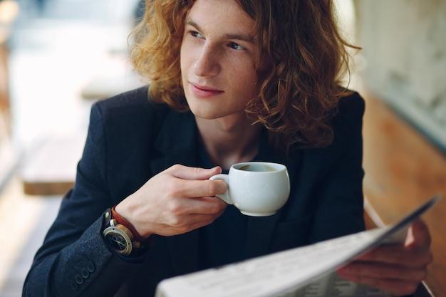 Jeune entrepreneur rougeâtre buvant du café en lisant