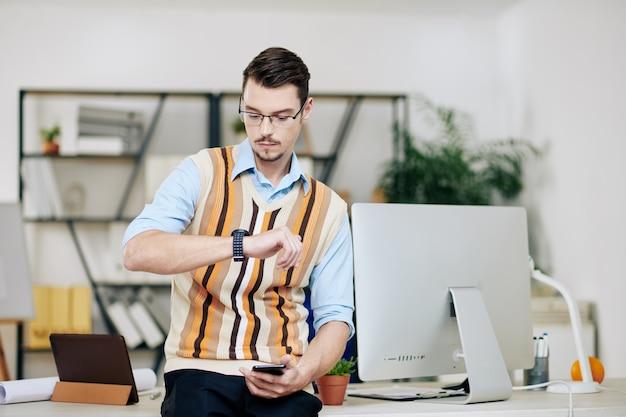 Jeune entrepreneur sérieux se tenant au bureau et vérifiant la smartwatch