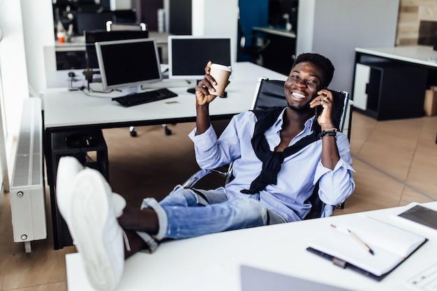 Jeune entrepreneur travaillant sur un projet dans un bureau moderne, tenant un café et se relaxant avec un téléphone.
