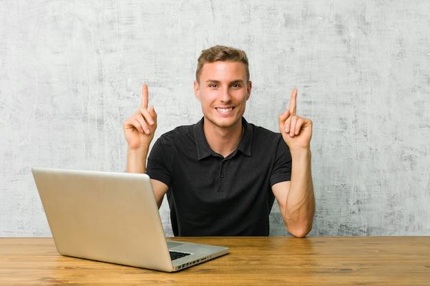 Un jeune entrepreneur travaillant avec son ordinateur portable sur un bureau indique avec les deux doigts antérieurs un espace vide.