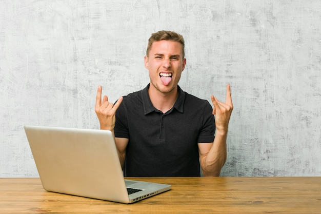 Jeune entrepreneur travaillant avec son ordinateur portable sur un bureau montrant un geste rock avec les doigts