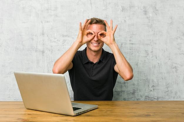 Jeune entrepreneur travaillant avec son ordinateur portable sur un bureau montrant un signe correct sur les yeux